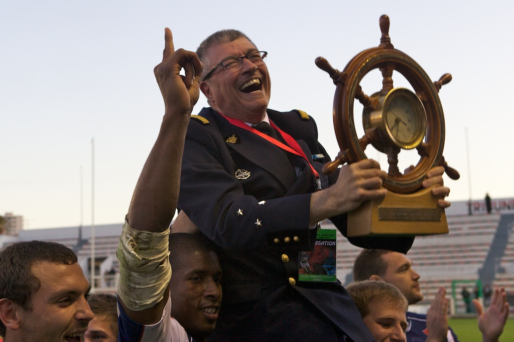 'Le Petit Amiral' – Jean-Claude Solue is lifted aloft with the Babcock International Trophy by the winning Marine Nationale team.
